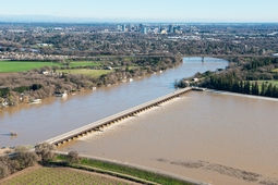 The Sacramento Weir opens its gates to flood the Sacramento Bypass Wildlife Area in Yolo County, Calif. on January 13, 2017.