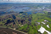 Aerial view looking east Holland Tract in foreground then Old river and Bacon Island in background, part of the Sacramento-San Joaquin River Delta in San Joaquin County, California.