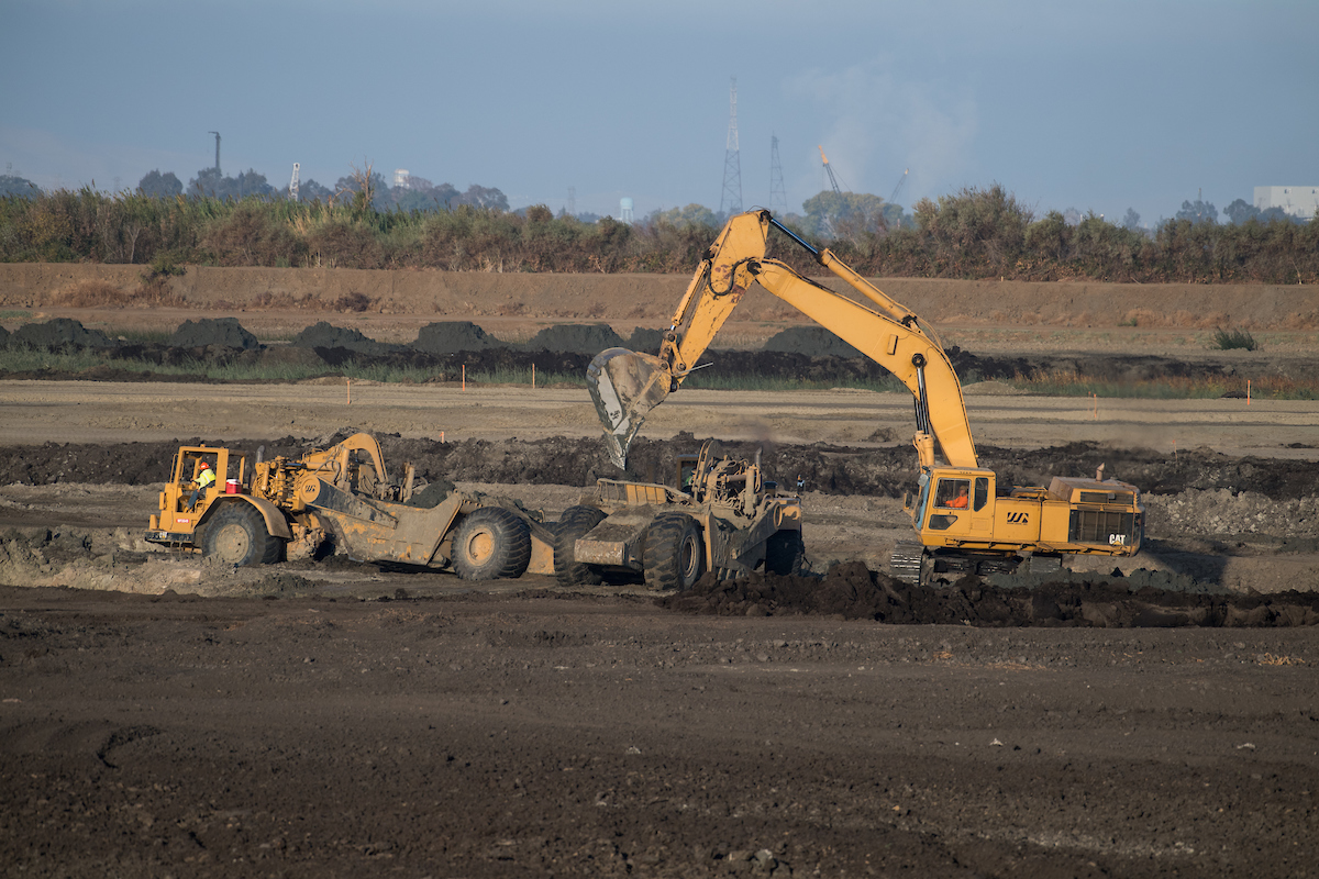 Construction equipment removes sand from a borrow pit to be place at the Dutch Slough Tidal Marsh Restoration Project in the Sacramento-San Joaquin Delta implemented by the California Department of Water Resources.