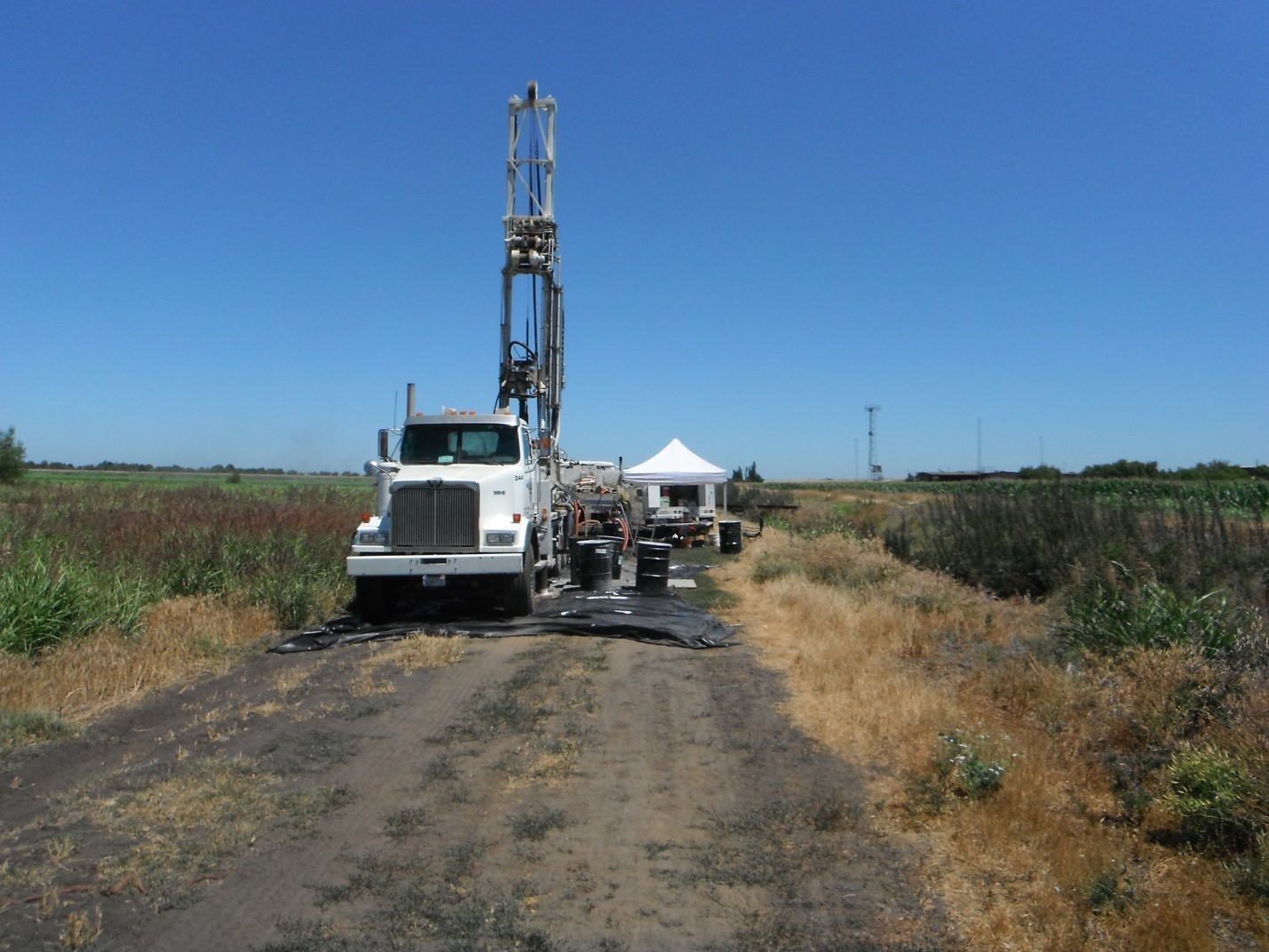 Photo of truck-mounted drill rig with support trucks and equipment used for soil exploration. A temporary tent structure by the drill rig is used to process soil samples and provide shade for the working crew.
