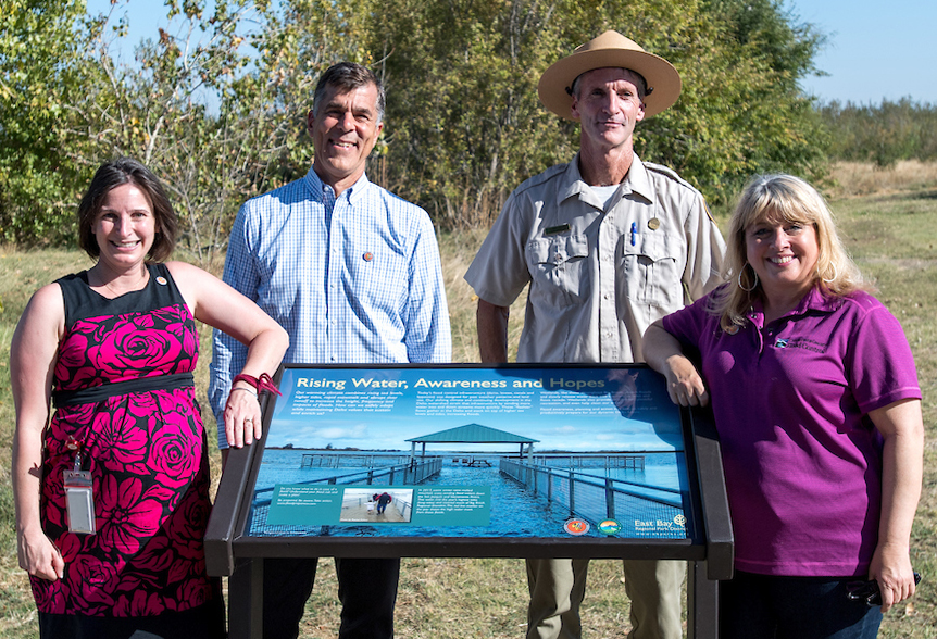 Photo of high water mark sign at Big Break Regional Park with partner agency officials