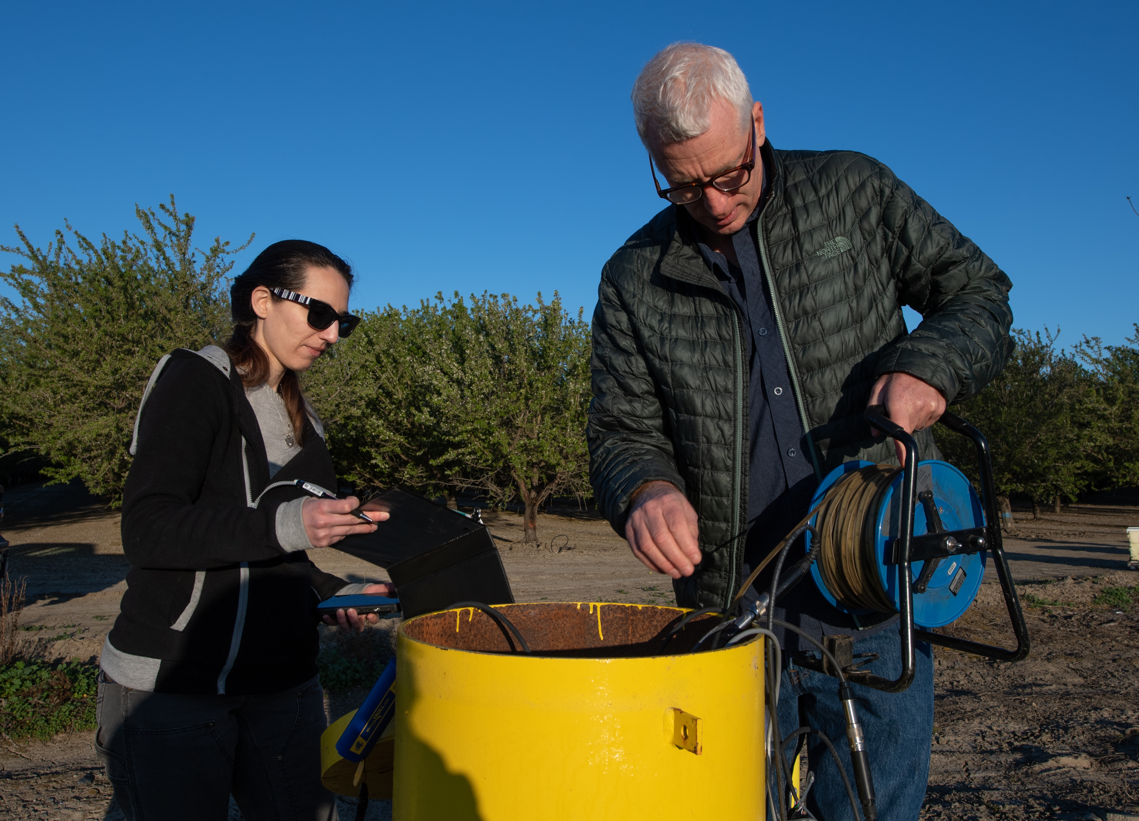 Department of Water Resources engineering geologists Aaron Cuthbertson (right) and Kimberly Bowman measure groundwater levels at a designated monitoring well, one of thousands of wells in California used to generate groundwater level change reports.