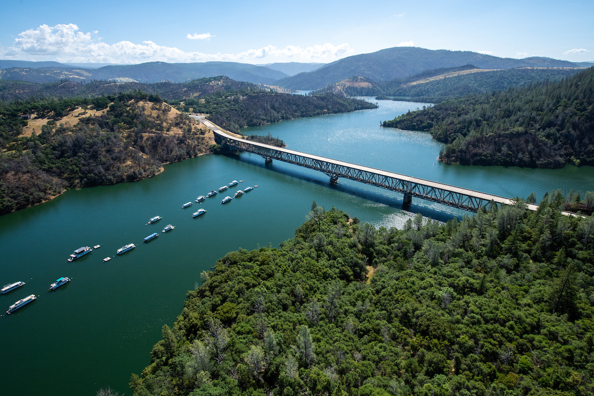 An aerial view of the Highway 70 bridge crossing over the Lake Oroville Marina, showing Lake Oroville.