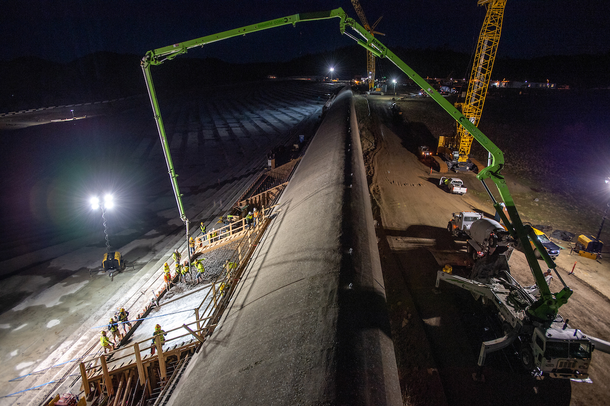 Before sunrise, workers from Kiewit Infrastructure pump structural concrete into forms as part of the finish work on the first section of a new concrete cap below the Lake Oroville emergency spillway weir.