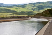 A section of the California Aqueduct within the California State Water Project, located near Wheeler Ridge, which convey California Aqueduct water between Ira J. Chrisman Wind Gap and Edmonston Pumping Plants within Kern County. In the background is the Tehachapi Mountains.