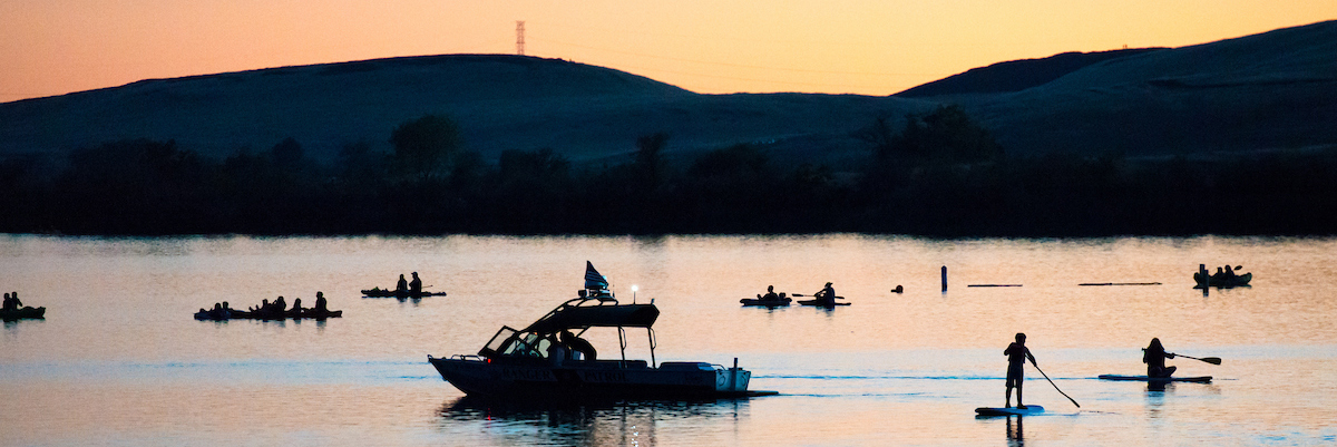 Boats, kayaks, and paddleboarders on Lake Oroville at sunset