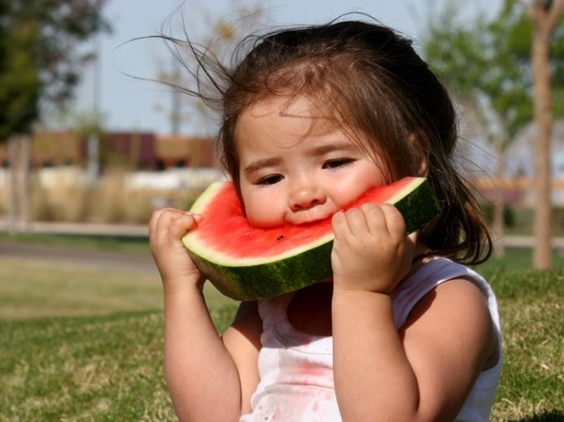 Photo of a child eating a slice of watermelon.