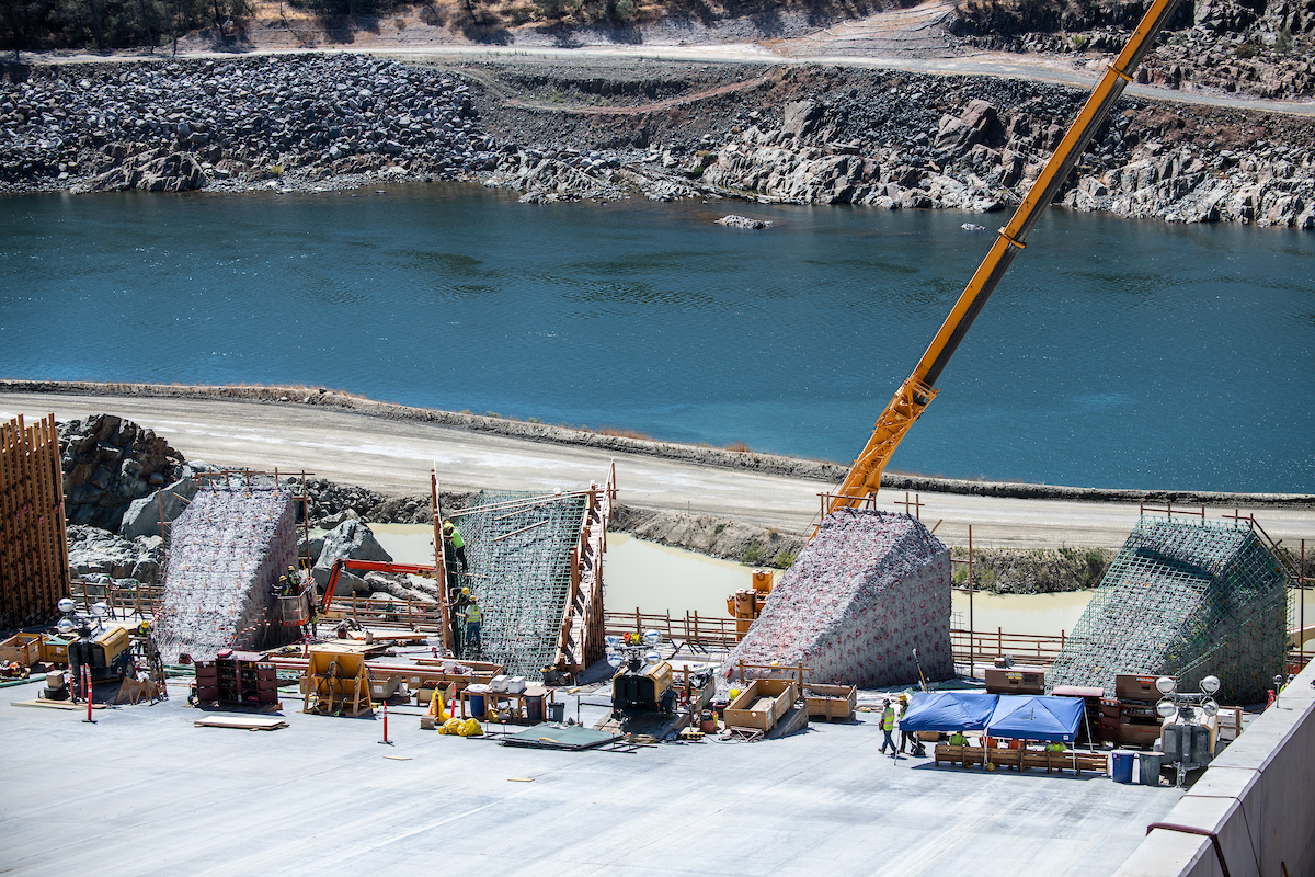 Workers prepare four energy dissipator blocks for new concrete surfaces on the lower chute of the Lake Oroville main spillway.